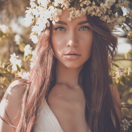 Portrait of beautiful romantic lady in a wreath of apple trees in the summer garden